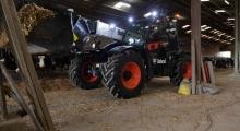 Телескопический погрузчик для сельского хозяйства Bobcat TL43.80HF+AGRI работает в коровнике.