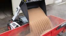 Телескопический погрузчик для сельского хозяйства Bobcat TL43.80HF+AGRI разгружает зерно в самосвал.