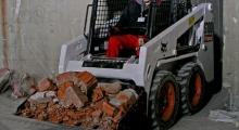 Колесный мини погрузчик Bobcat S100 грузит камни