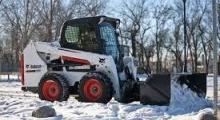 Колесный мини погрузчик Bobcat S550 расчищает снег
