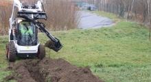 Колесный мини погрузчик Bobcat S570 роет траншею