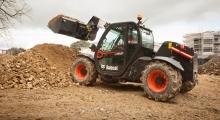 Телескопический погрузчик для сельского хозяйства Bobcat TL26.60+AGRI выгружает песок