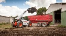 Телескопический погрузчик для сельского хозяйства Bobcat TL35.70+AGRI выгружает землю
