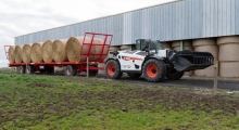 Телескопический погрузчик для сельского хозяйства Bobcat TL43.80HF+AGRI перемещает прицеп со снопами по ферме.