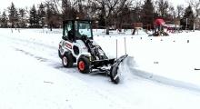 Шарнирно-сочлененный погрузчик Bobcat L28 убирает снег