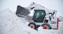 Колесный мини погрузчик Bobcat S570 убирает снег