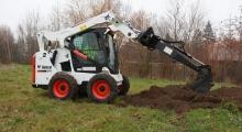 Колесный мини погрузчик Bobcat S570 копает землю